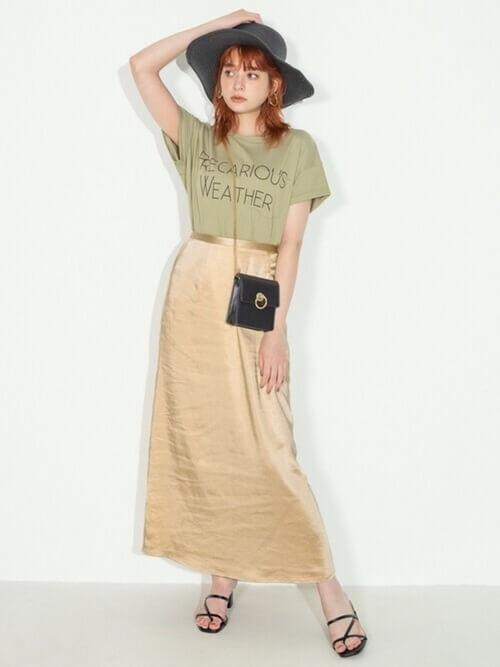 グリーンのロゴTシャツ×ベージュのスカート×黒のサンダル