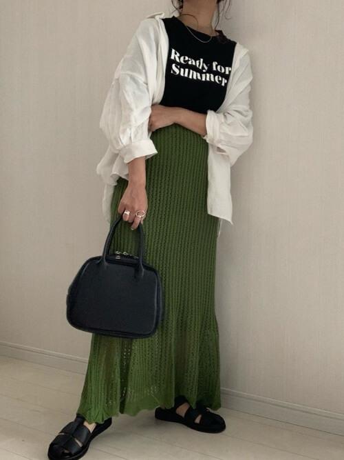 グルカサンダル×グリーンの透かし編みニットスカート×白のシャツ×黒のロゴTシャツ