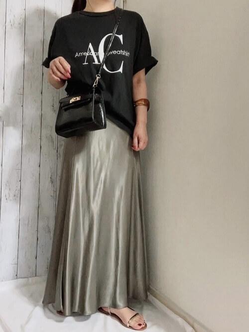 黒のロゴTシャツ×グリーンのサテン風スカート×ゴールドのサンダル×黒のショルダーバッグ