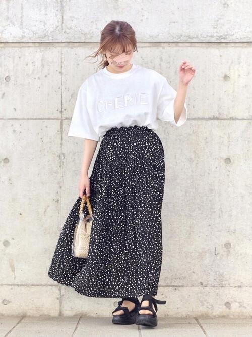 白のロゴTシャツ×黒の花柄スカート×黒のサンダル×クリアバッグ