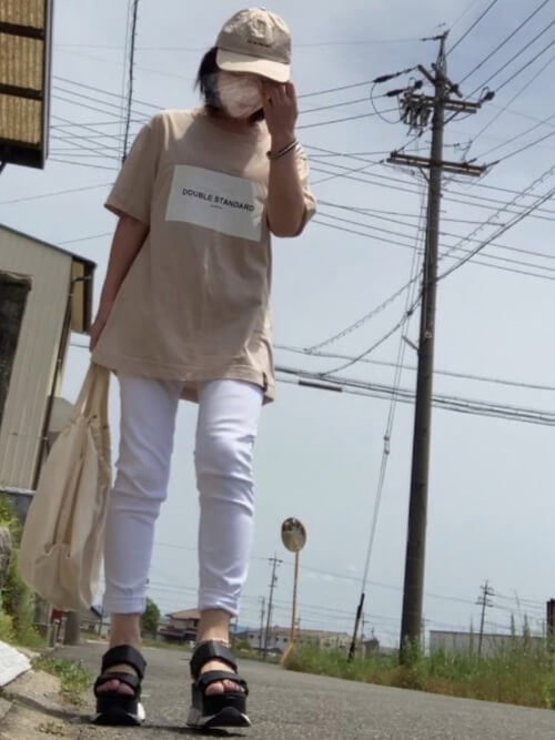 白のスキニーパンツ×ベージュのTシャツ×黒のサンダル×トートバッグ