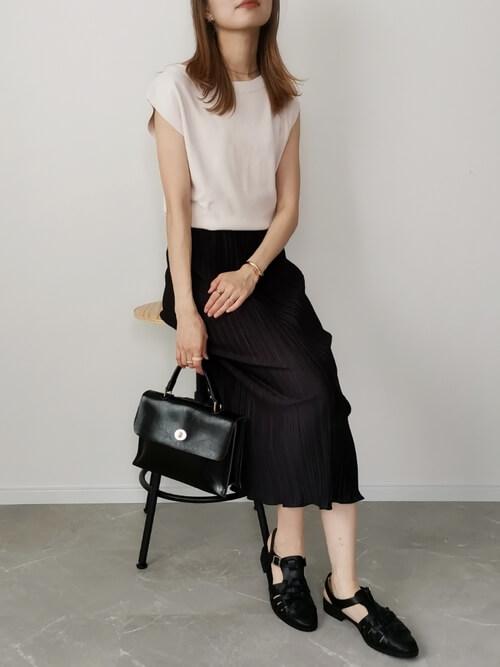黒のプリーツスカート×ベージュのニット×黒のグルカサンダル×黒のバッグ