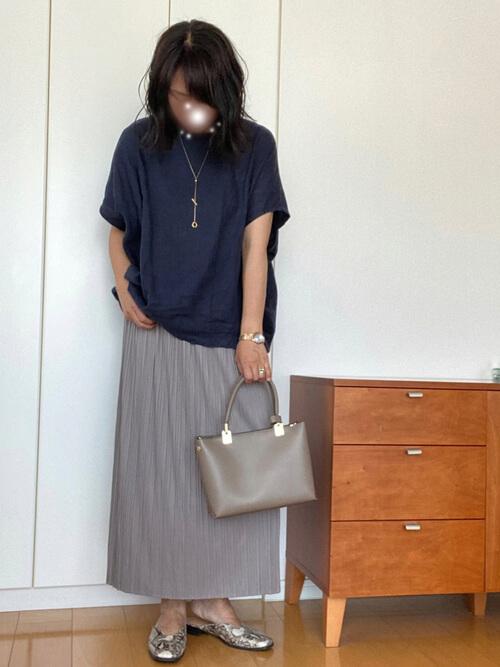 グレーのプリーツスカート×ネイビーのTシャツ×バイソン柄のパンプス×グレーのバッグ