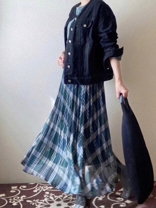 チェックのプリーツスカート×黒のデニムジャケット×グリーンのTシャツ×黒のトートバッグ