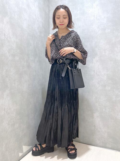 黒のプリーツスカート×総柄ブラウス×黒の厚底サンダル×黒のベルト×黒のショルダーバッグ