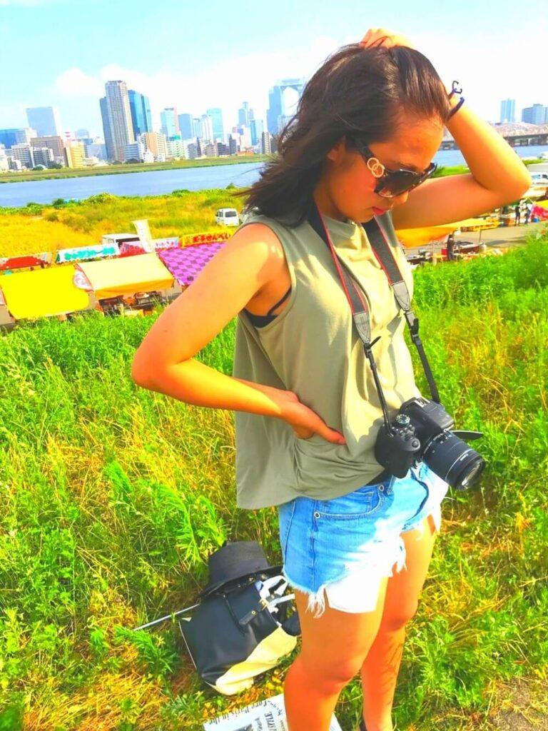 カーキのタンクトップ×デニムショートパンツのカメラ女子コーデ