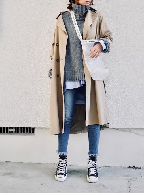 ニットセーター×ベージュのトレンチコート×ストライプシャツ×デニムパンツ×黒のスニーカー