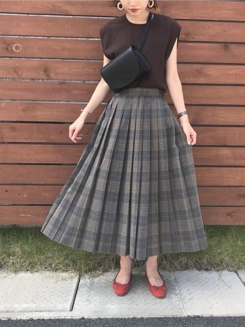 チェックのプリーツスカート×ブラウンの半袖ニット×オレンジのパンプス×黒のウエストポーチ