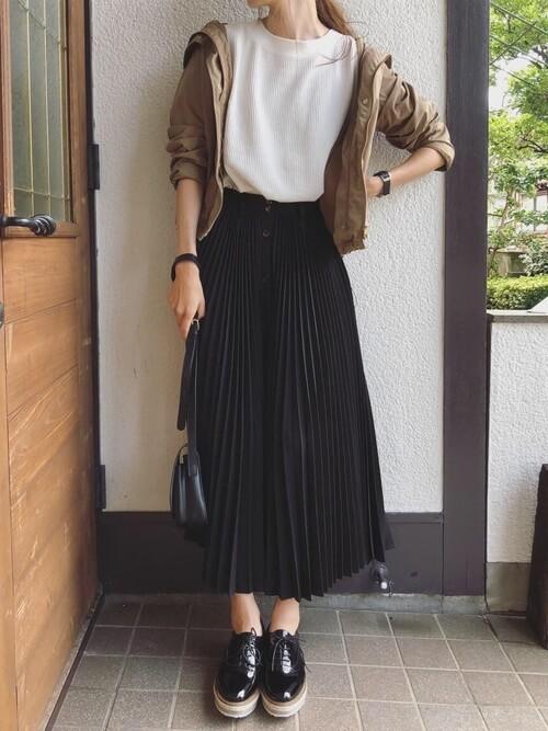 黒のプリーツスカート×ベージュのジャケット×白のTシャツ×黒のブーツ