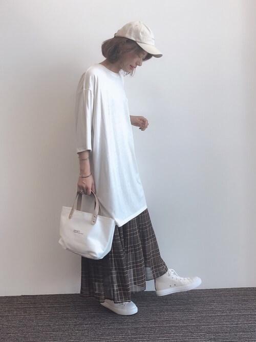 チェックのプリーツスカート×白のチュニック×白のスニーカー×ベージュのキャップ