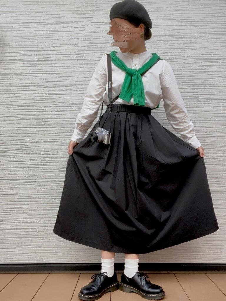 白のバンドカラーシャツ×緑のカーディガン×黒のフレアスカート×ローファーのカメラ女子コーデ