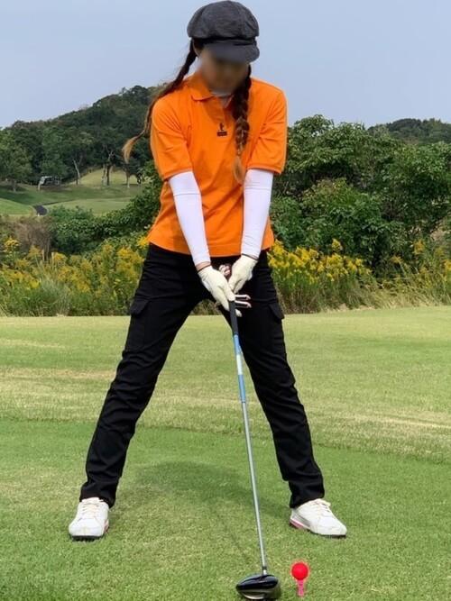 オレンジのポロシャツ×白のインナー×黒のパンツ×黒のハンチング