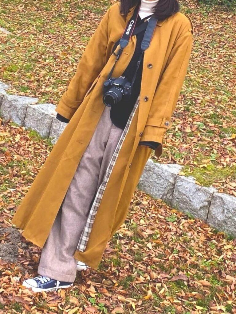 白のハイネック×黒のニット×茶色のワイドパンツ×ステンカラーコートのカメラ女子コーデ