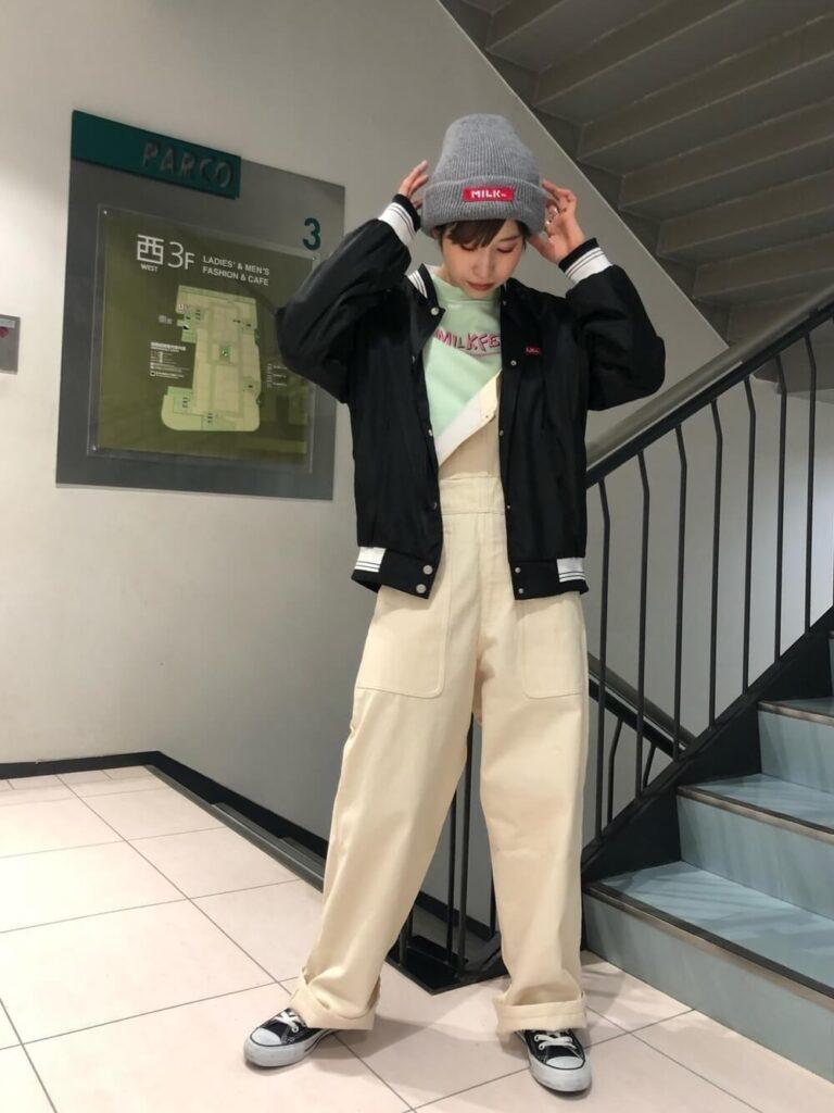グリーンのTシャツ×白のサロペット×スニーカー×黒スタジャンのレディースコーデ