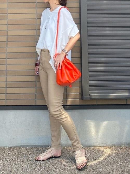ベージュのスキニーパンツ×白のTシャツ×ベージュのフリンジサンダル×オレンジのショルダーバッグ