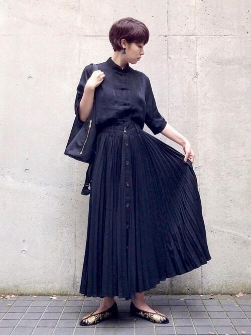 ネイビーのプリーツスカート×黒のチャイナシャツ×ゴールドのパンプス×黒のバッグ
