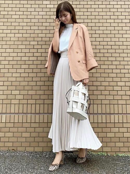 ピンクのテーラードジャケット×白のブラウス×ベージュのプリーツスカート×チェックのパンプス