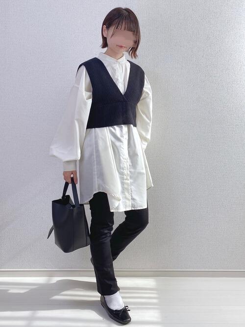 スキニーパンツ×白のロング丈シャツ×黒のニットビスチェ×黒のバレエシューズ