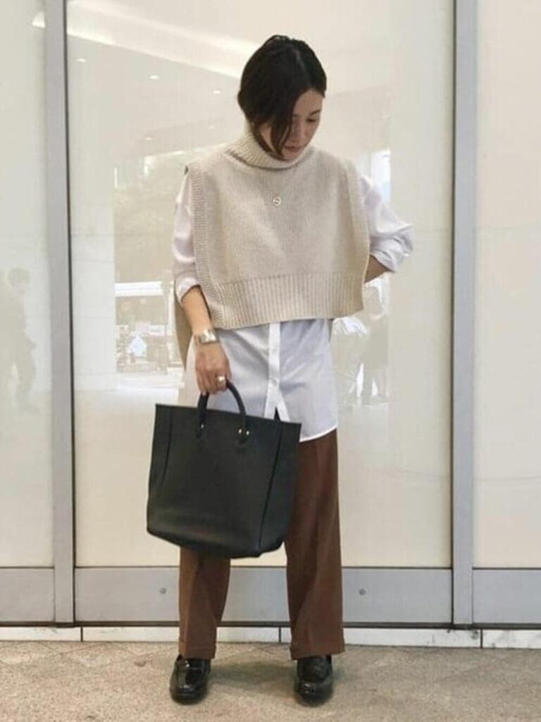 白シャツ×ベスト風ニット×茶色のストレートパンツ×ローファーの秋のオフィスコーデ
