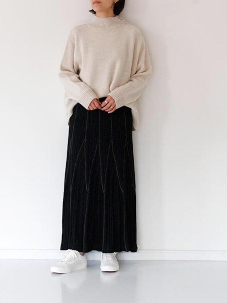 黒のフレアスカート×白のスニーカー×ベージュのニット・セーターの秋コーデ