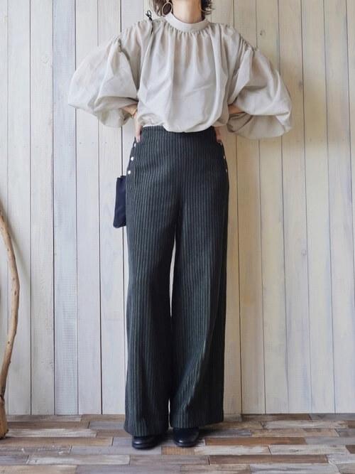 グリーンのコーデュロイパンツ×ベージュのブラウス×黒のブーツ