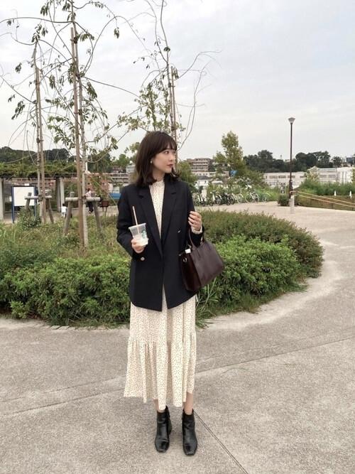 黒のテーラードジャケット×白のドット柄ワンピース×黒のブーツ