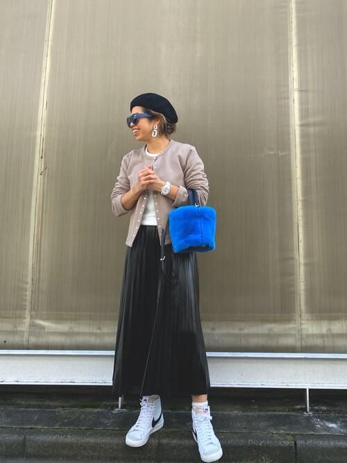 黒のプリーツスカート×ベージュのカーディガン×白のスニーカー×青のバッグ