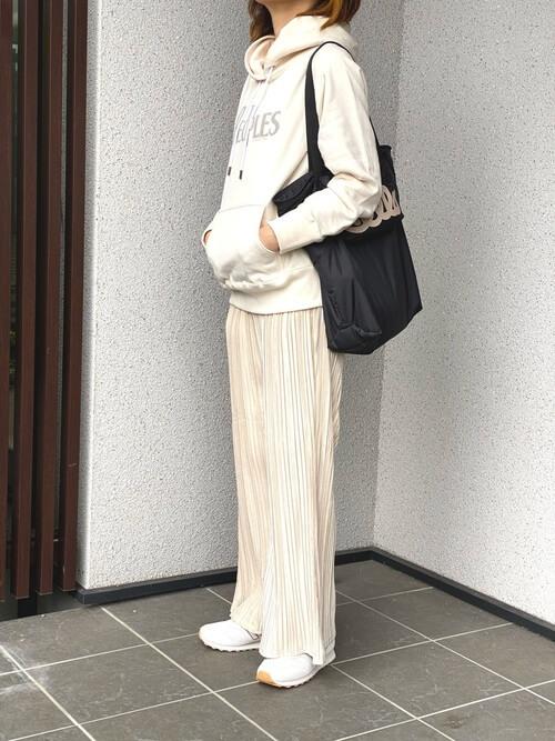 白のパーカー×ベージュのプリーツパンツ×白のスニーカー×黒のトートバッグ