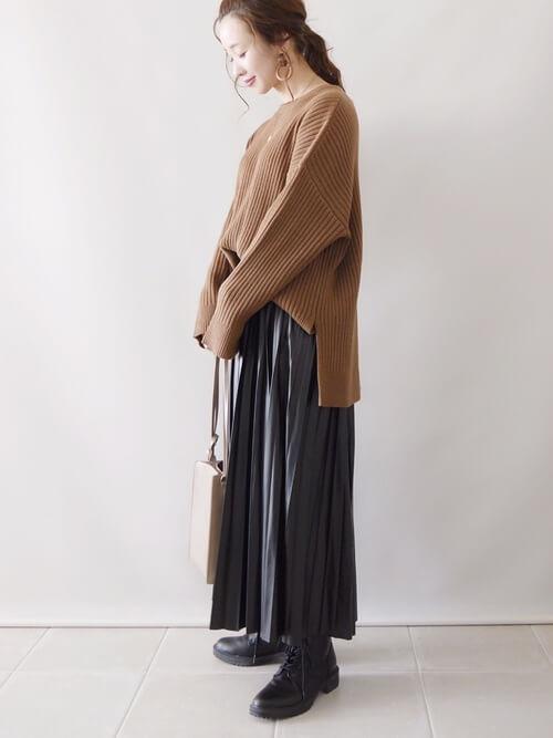 黒のプリーツスカート×ブラウンのニット×黒のブーツ×ベージュのバッグ