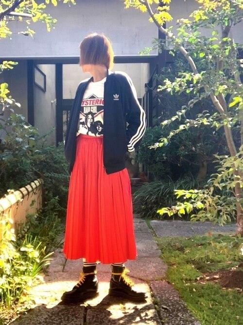 赤のプリーツスカート×黒のトラックジャケット×白のロゴTシャツ×黒のブーツ