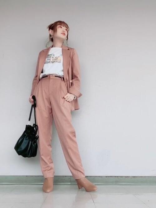ピンクのジャケット×白のプリントTシャツ×ピンクのパンツ×ベージュのブーツ×黒のバッグ