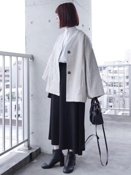 黒のショートブーツ×白のノーカラーコート×白のブラウス×黒のスカート×黒のバッグ