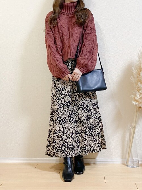 黒のショートブーツ×ピンクのタートルネックニット×黒の花柄スカート×黒のショルダーバッグ