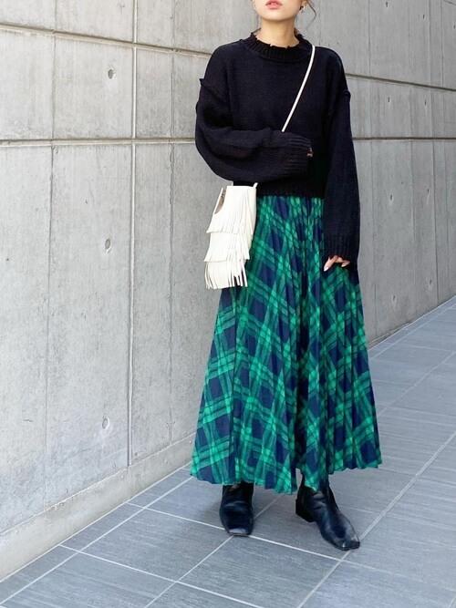 チェックのプリーツスカート×黒のニット×黒のブーツ×白のフリンジバッグ