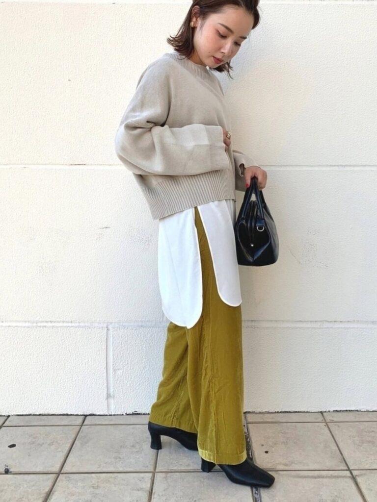 白シャツ×黄色のベロアパンツ×黒のブーツ×ベージュのニット・セーターの秋コーデ