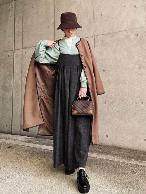 ハット×ブラウンのノーカラーコート×グリーンのキーネックニット×黒のサロペットスカート×黒のローファー
