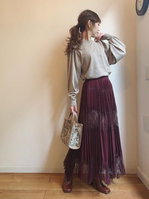 赤のプリーツスカート×ベージュのニット×ブラウンのブーツ×ベージュのバッグ