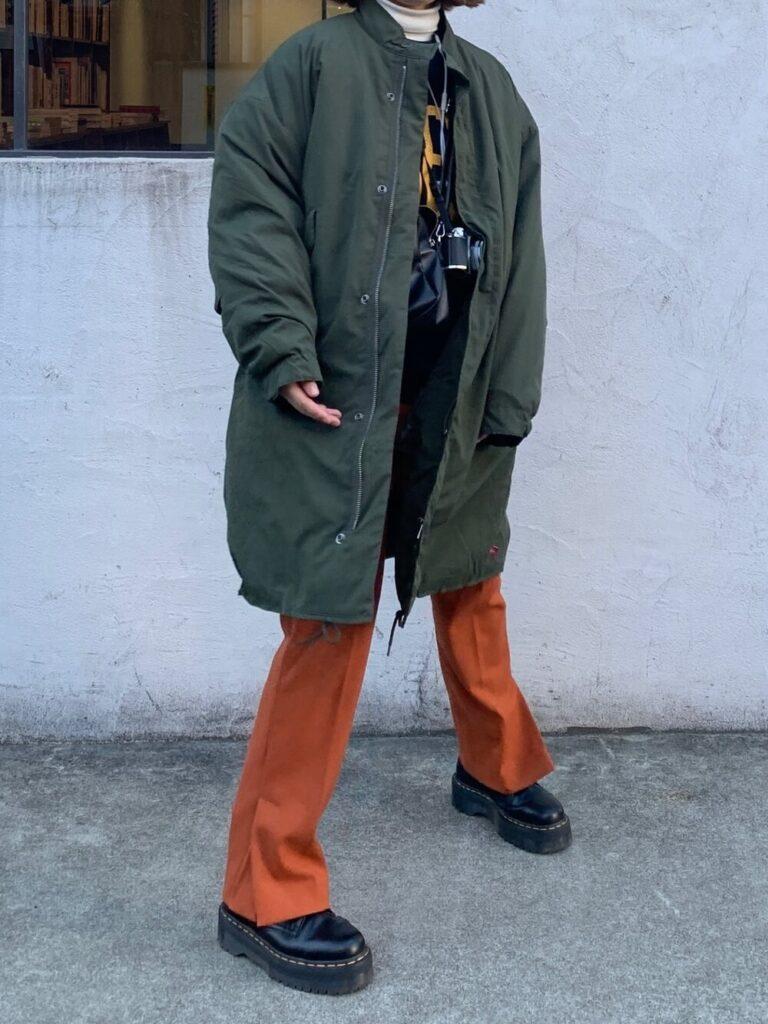 スウェット×オレンジのフレアパンツ×モッズコート×ショーツブーツのカメラ女子コーデ