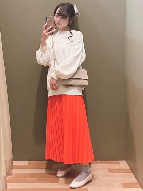 赤のプリーツスカート×白のトレーナー×白のパンプス×ベージュのバッグ