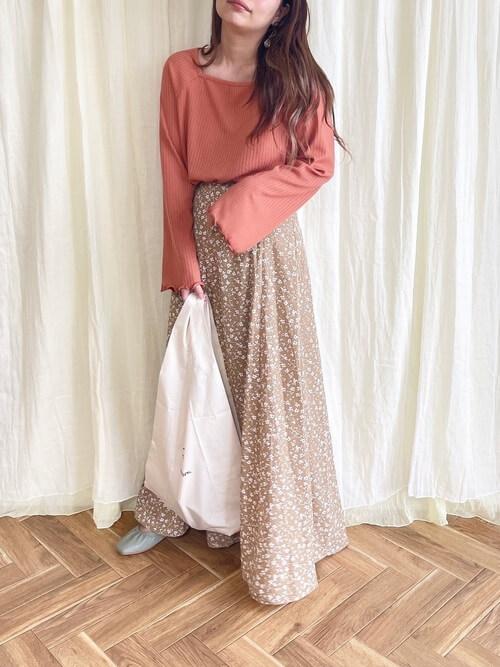 テラコッタのニット×ブラウンのスカート×グレーのパンプス×白のバッグ