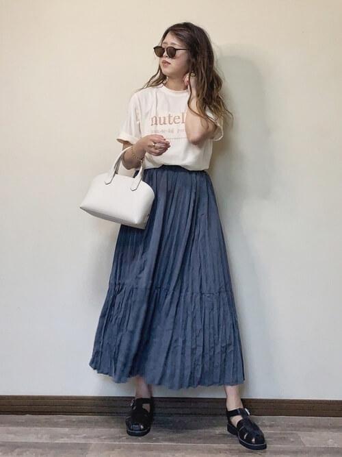 ネイビーのプリーツスカート×ベージュのロゴTシャツ×黒のグルカサンダル×白のバッグ