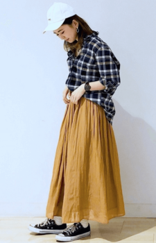 ネイビーシャツ×マスタードカラーのロングスカート×黒のスニーカー×キャップ