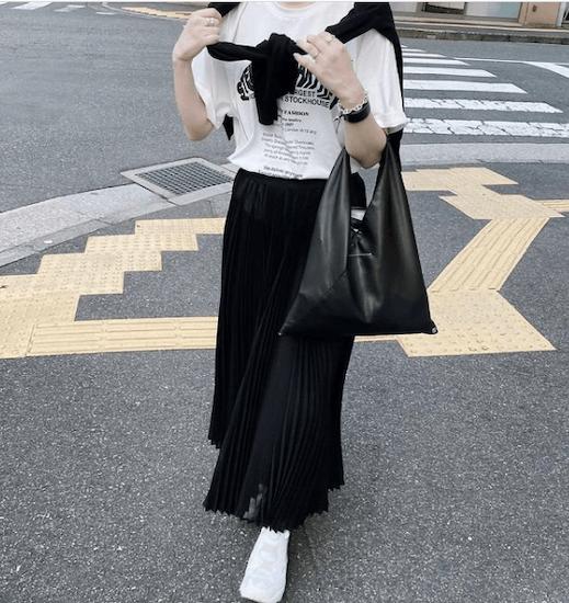 黒のプリーツスカート×黒のカーディガン×白のロゴTシャツ×白のスニーカー