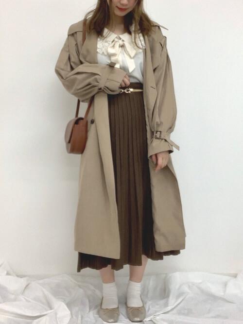 トレンチコート×白のリボンブラウス×ブラウンのプリーツスカート×シルバーのパンプス