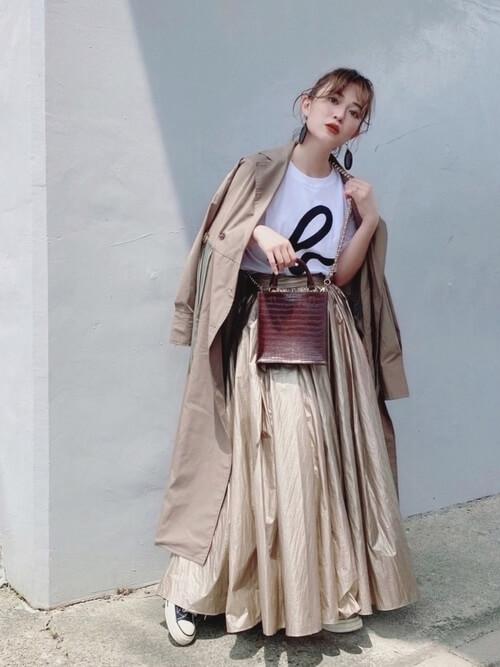 トレンチコート×白のロゴTシャツ×ベージュのスカート×黒のスニーカー