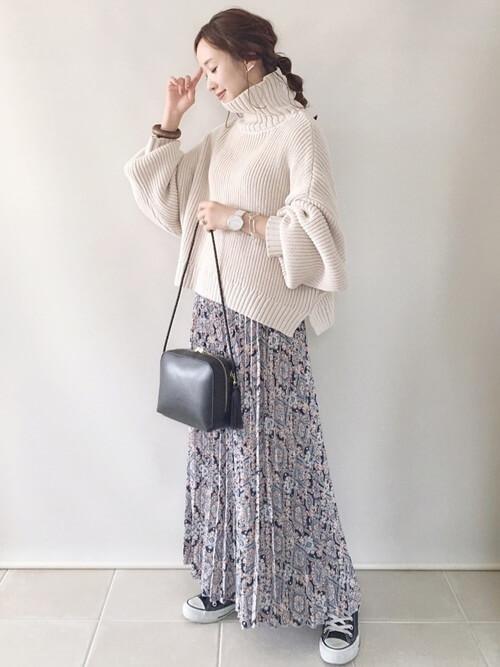 白のリブニット×ブルーの花柄スカート×黒のスニーカー×黒のバッグ