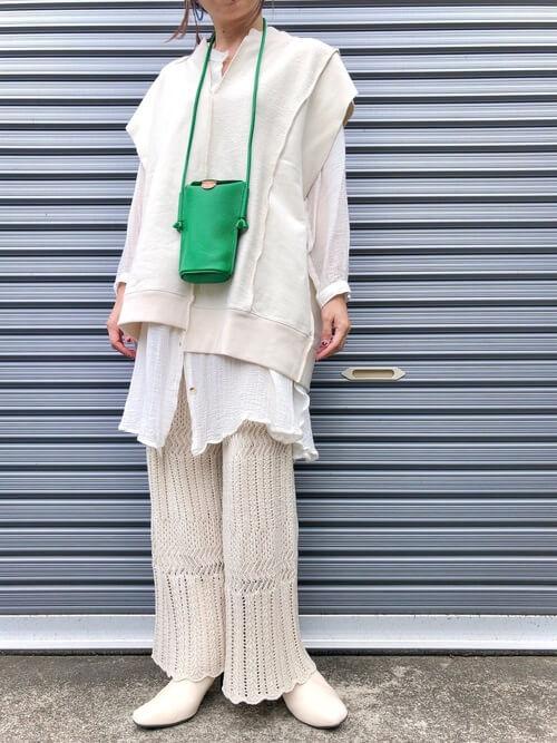 白のブーツ×白のベスト×白のシャツ×ベージュの編み上げパンツ×グリーンのバッグ