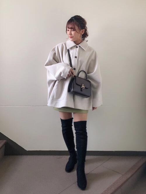 黒のニーハイブーツ×白のポンチョコート×グリーンのスカート×黒のバッグ