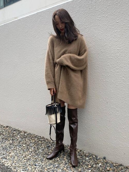 茶色のロングブーツ×ベージュのニットワンピース×白のバッグ
