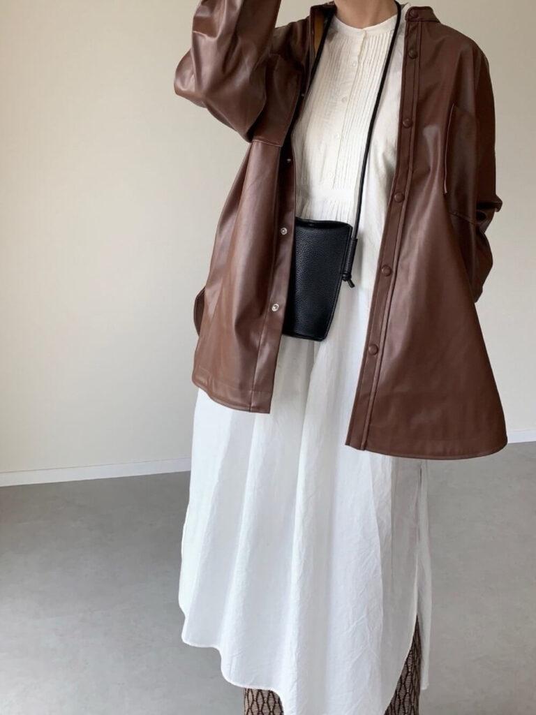 ブラウンのライダースジャケット×白のシャツワンピース×ジャガードニットパンツ×黒のバレエシューズ